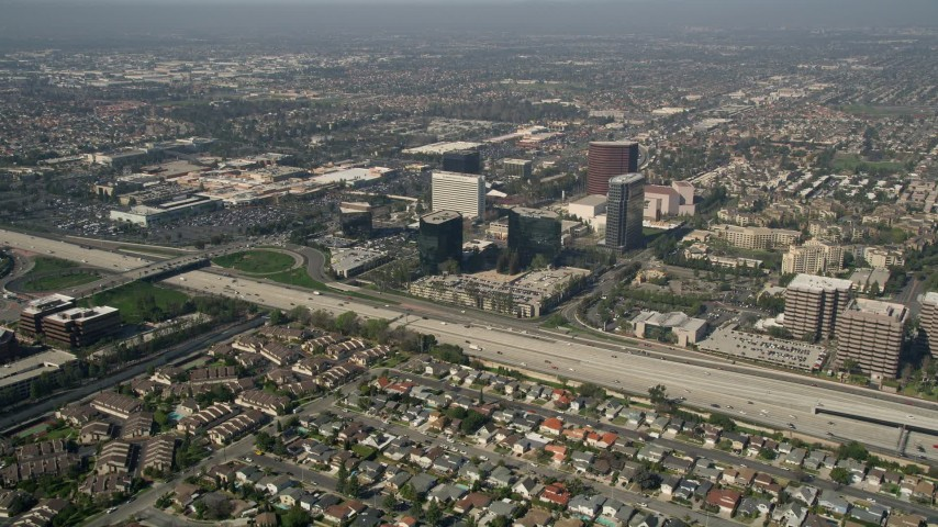 5K stock footage aerial video fly over homes to approach office buildings on the other side of Interstate 405, Costa Mesa, California Aerial Stock Footage | AX0016_085E