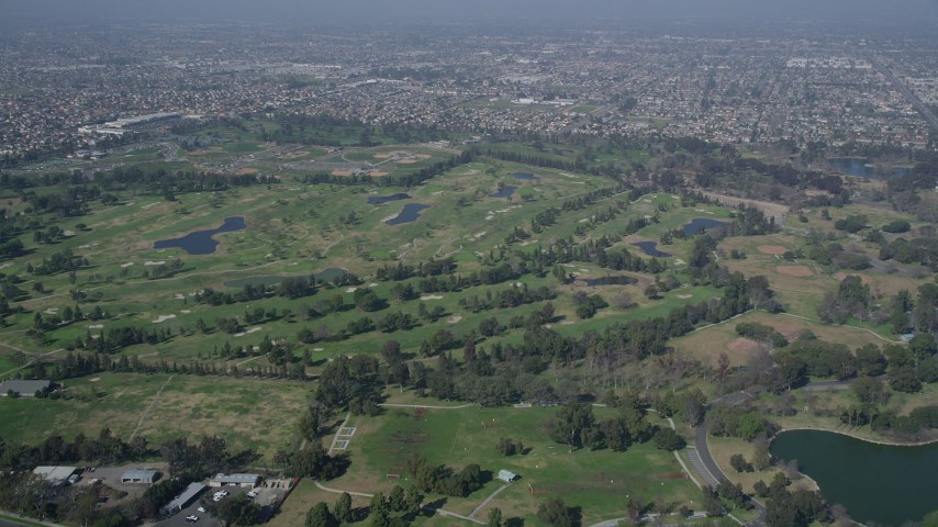 5K stock footage aerial video approach and tilt down to Mile Square Golf Course, Fountain Valley, California Aerial Stock Footage | AX0016_093
