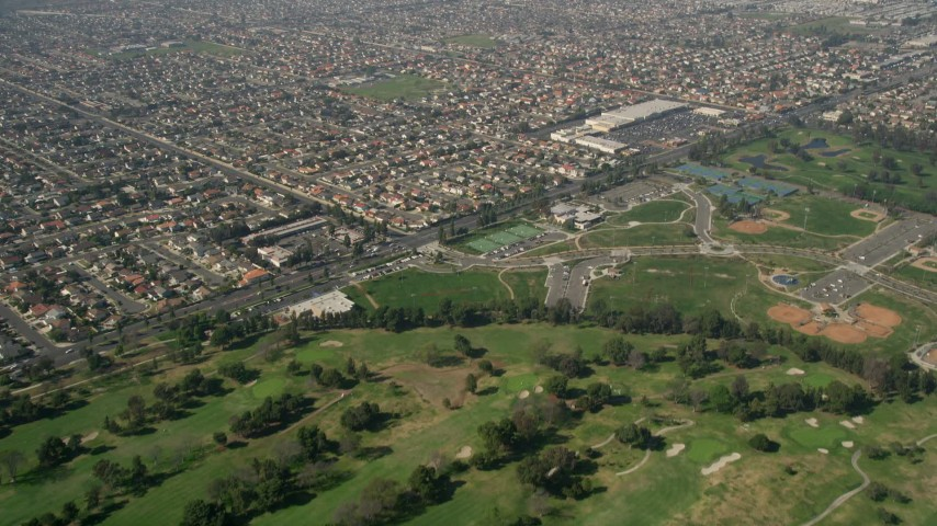 5K stock footage aerial video fly over Mile Square Golf Course, to and approach residential neighborhoods, Fountain Valley, California Aerial Stock Footage | AX0016_094
