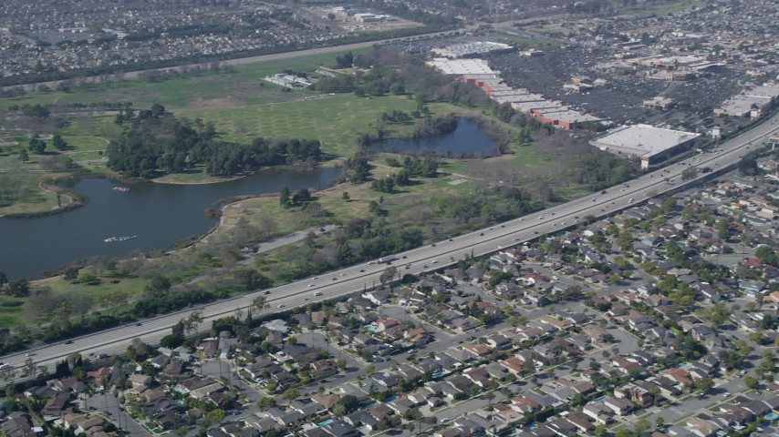 5K aerial video of track light traffic on I-605 by Long Beach Town Center and El Dorado East Regional Park, Long Beach, California Aerial Stock Footage AX0016_103