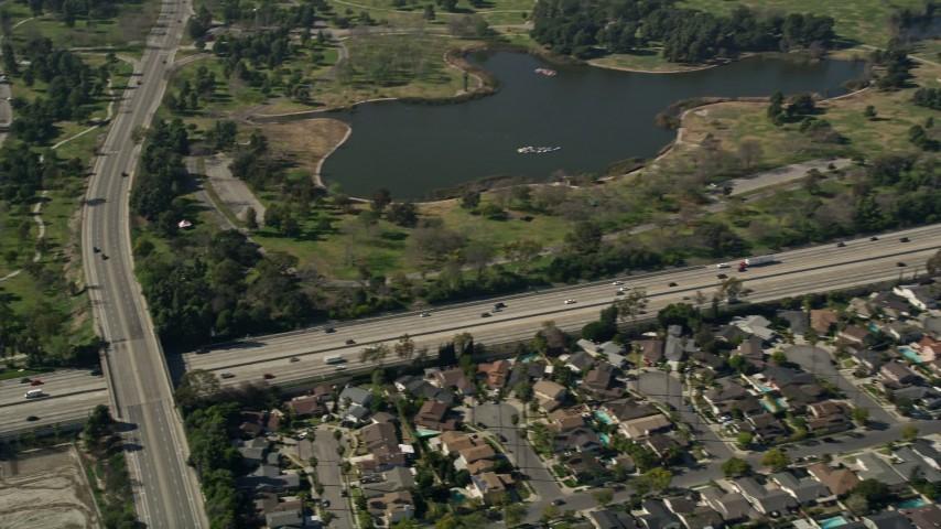 5K stock footage aerial video of track light traffic on I-605 by Long Beach Town Center and El Dorado East Regional Park, Long Beach, California Aerial Stock Footage | AX0016_103E