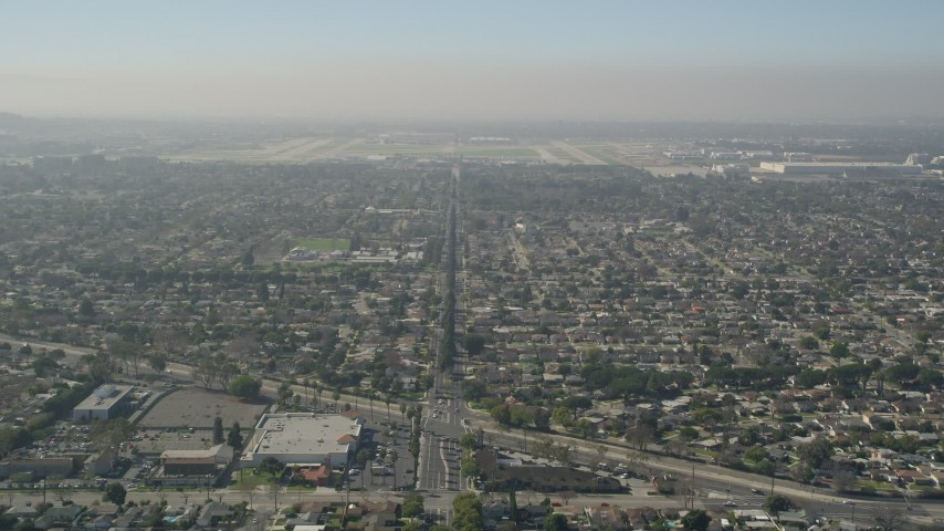 5K aerial video tilt from East Warlow Road through neighborhoods to reveal and approach Long Beach Airport, California Aerial Stock Footage | AX0016_105
