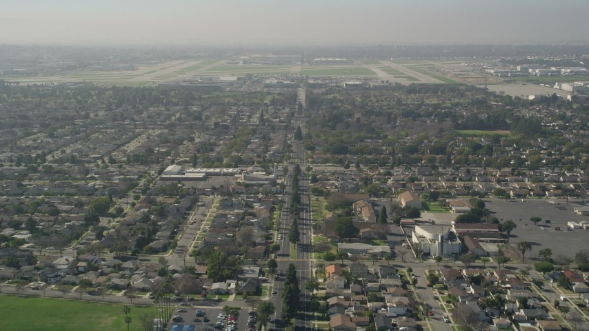 5K stock footage aerial video tilt up East Warlow Road to reveal and approach neighborhoods and Long Beach Airport, California Aerial Stock Footage   AX0016_106