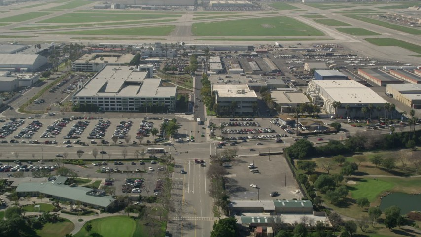 5K stock footage aerial video tilt from East Warlow Road to reveal and approach parking garage at Long Beach Airport, California Aerial Stock Footage | AX0016_109E