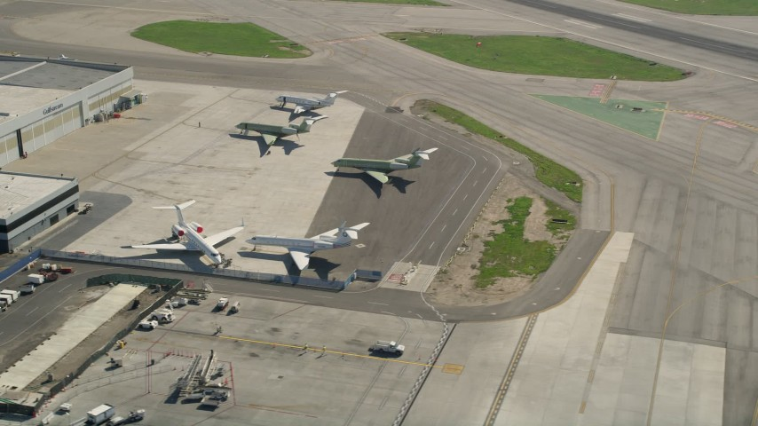 5K aerial video of civilian jets parked near a hangar at Long Beach Airport, California Aerial Stock Footage | AX0016_112