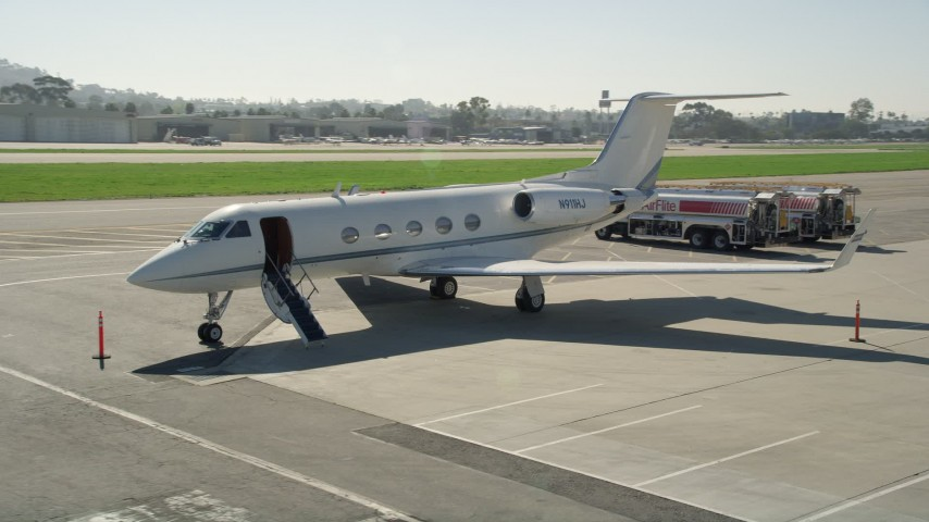 5K stock footage aerial video approach and land next to a private jet, Long Beach Airport, California Aerial Stock Footage AX0016_115 | Axiom Images