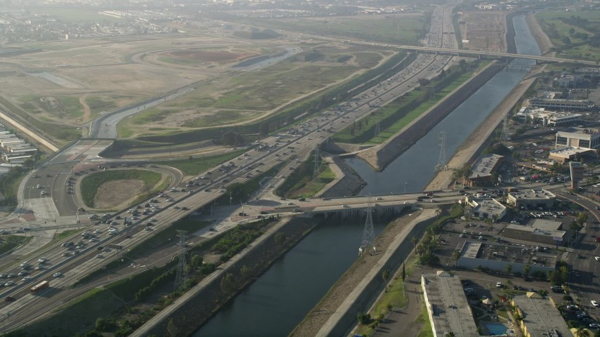 5K stock footage aerial video fly over heavy interstate traffic along a river, Carson, California Aerial Stock Footage | AX0017_010