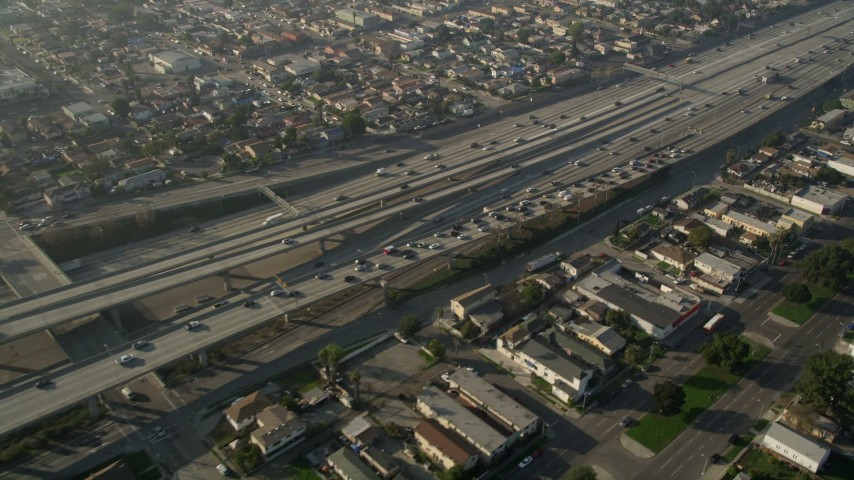 5K stock footage aerial video of following Interstate 110 with heavy traffic through neighborhoods, Westmont, California Aerial Stock Footage | AX0017_034