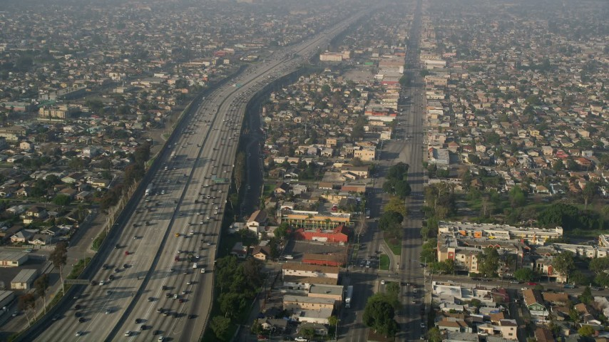 5K aerial video of following Broadway and Interstate 110 past residential neighborhoods, South Central Los Angeles Aerial Stock Footage AX0017_035