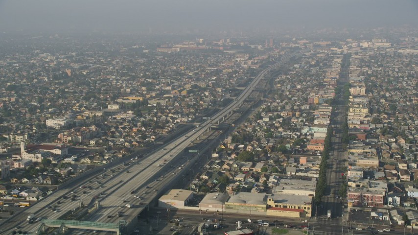 5K aerial video of Interstate 110 with traffic, tilt to reveal neighborhoods, South Central Los Angeles Aerial Stock Footage | AX0017_039