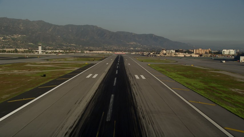5K stock footage aerial video of lifting off from Bob Hope International Airport revealing a passenger jet, Burbank, California Aerial Stock Footage AX0017_113 | Axiom Images