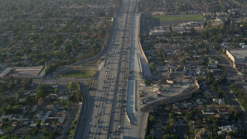 5K stock footage aerial video of following heavy interstate traffic through neighborhoods, Pacoima, California, sunset Aerial Stock Footage | AX0017_117