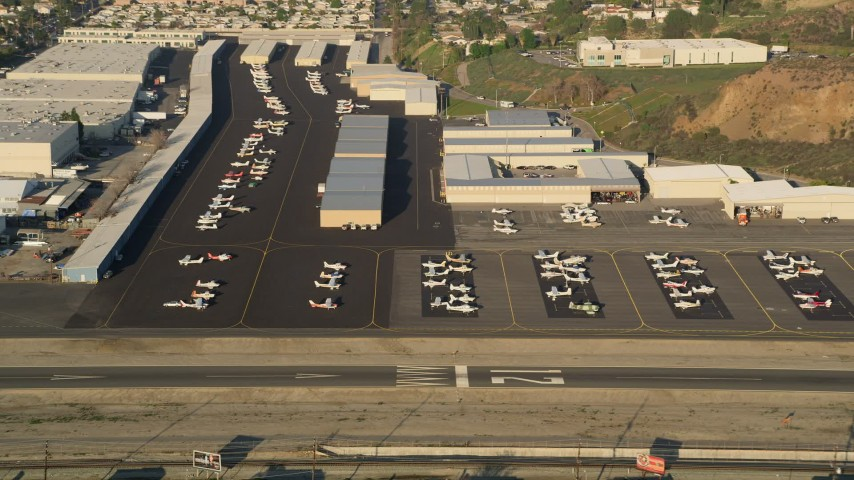 5K stock footage aerial video of Whiteman Airport, tilt to parked airplanes, Pacoima, California, sunset Aerial Stock Footage AX0017_118 | Axiom Images