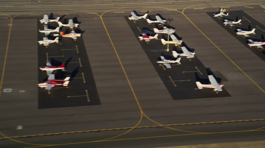 5K stock footage aerial video of airplanes on the tarmac at Whiteman Airport, Pacoima, California, sunset Aerial Stock Footage | AX0017_119