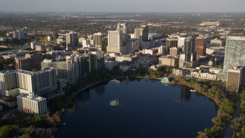 5K stock footage aerial video fly over Lake Eola to approach buildings in Downtown Orlando at sunrise, Florida Aerial Stock Footage | AX0018_004