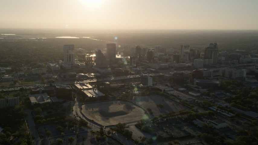 5K stock footage aerial video orbit Downtown Orlando with rising sun in the distance in Florida Aerial Stock Footage | AX0018_010