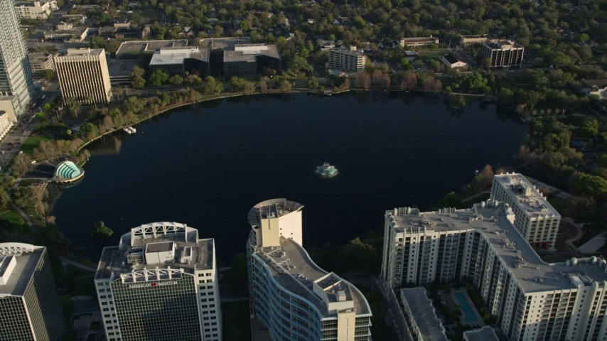 5K stock footage aerial video tilt and approach Lake Eola in Downtown Orlando at sunrise in Florida Aerial Stock Footage | AX0018_020