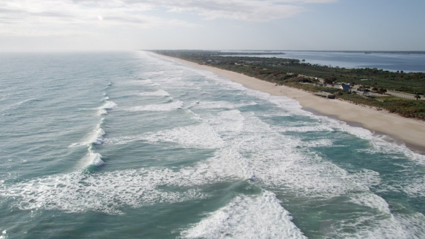 5K stock footage aerial video fly over ocean waves by Melbourne Beach in Florida Aerial Stock Footage | AX0018_074