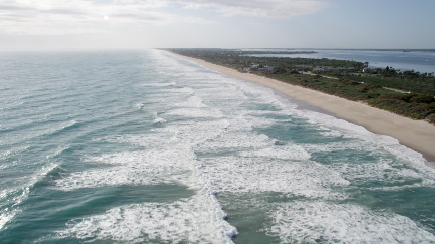 5K stock footage aerial video of flying over waves in Melbourne Beach, Florida Aerial Stock Footage | AX0018_075