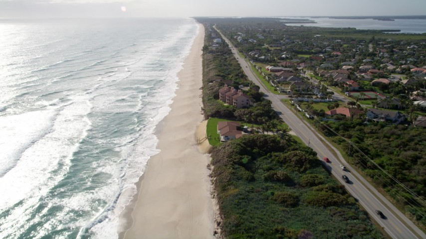 5K stock footage aerial video fly over sandy beach and homes in Melbourne Beach, Florida Aerial Stock Footage | AX0018_080
