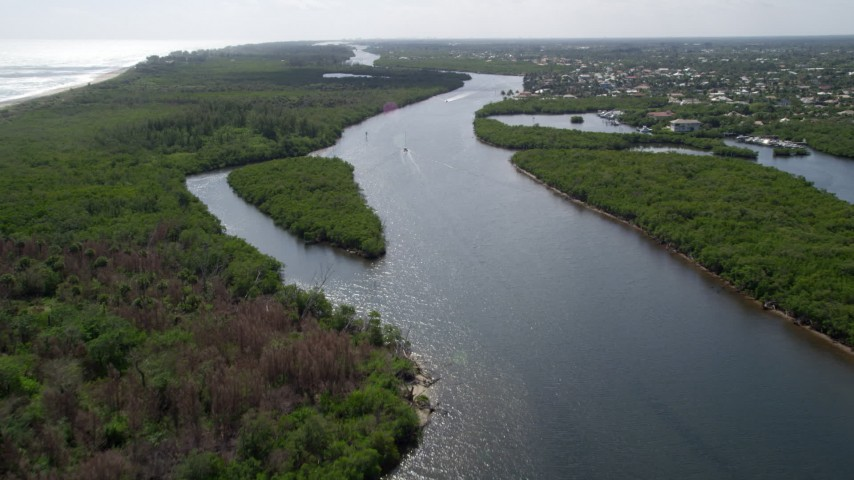 5K stock footage aerial video fly over the Indian River through Hobe Sound to approach sailboat, Florida Aerial Stock Footage | AX0019_009