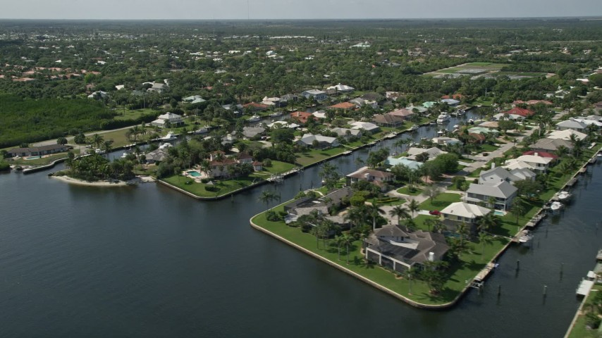 5K stock footage aerial video of waterfront homes on canals in Hobe Sound, Florida Aerial Stock Footage | AX0019_011