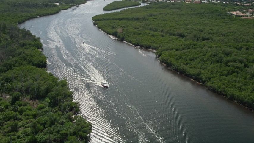 5K stock footage aerial video approach and tilt to fishing boat on the Indian River through Hobe Sound, Florida Aerial Stock Footage | AX0019_012