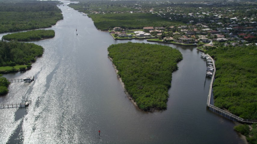 5K stock footage aerial video fly over Indian River and pan to approach waterfront homes in Hobe Sound, Florida Aerial Stock Footage | AX0019_013