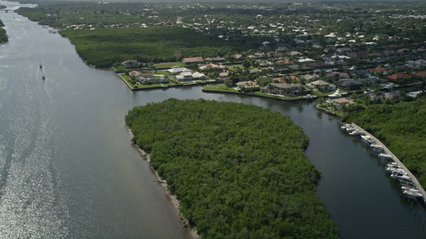 5K stock footage aerial video fly over Indian River and pan to approach waterfront homes in Hobe Sound, Florida Aerial Stock Footage | AX0019_013E