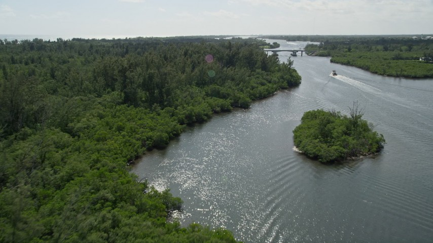 5K stock footage aerial video approach and fly over mangroves lining the Indian River near bridge in Hobe Sound, Florida Aerial Stock Footage | AX0019_015E
