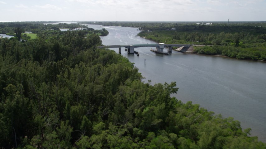 5K stock footage aerial video fly over mangroves to approach small bridge over the Indian River in Florida Aerial Stock Footage | AX0019_017