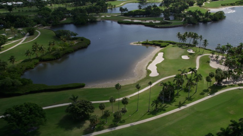 5K aerial video of flying by palm trees at the Jupiter Island Golf Club in Hobe Sound, Florida  Aerial Stock Footage | AX0019_019