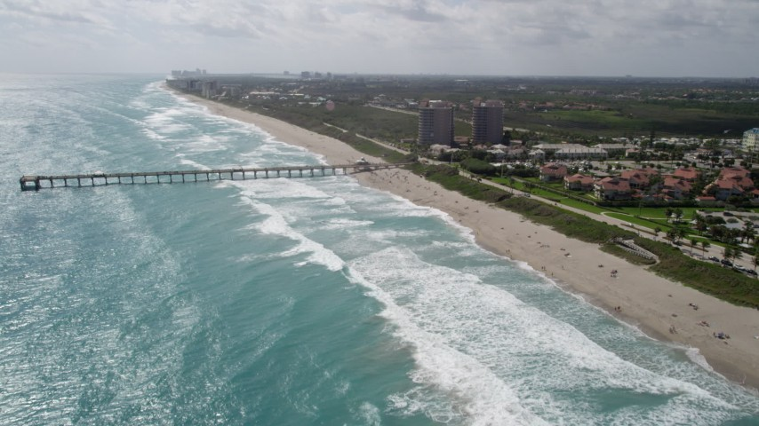 5K stock footage aerial video approach pier and beachgoers in Juno Beach, Florida Aerial Stock Footage | AX0019_043