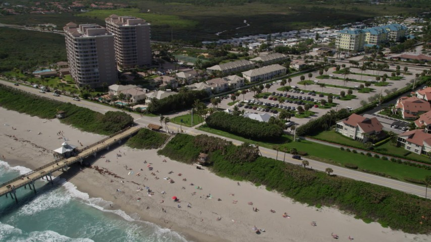 5K stock footage aerial video of sunbathers on the beach and beachfront homes in Juno Beach, Florida Aerial Stock Footage | AX0019_044