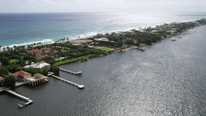 5K stock footage aerial video of passing waterfront mansions with docks on Lake Worth in Palm Beach, Florida  Aerial Stock Footage | AX0019_069