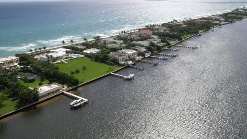 5K aerial video of lakefront mansions with docks and ocean views in Palm Beach, Florida Aerial Stock Footage | AX0019_070