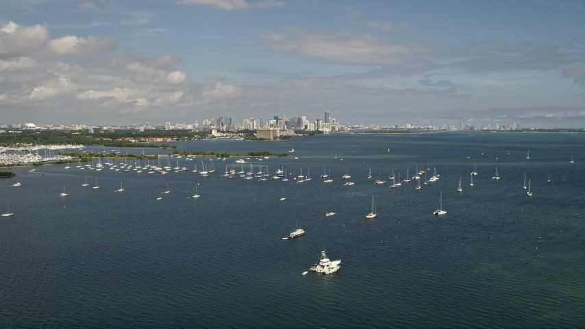 5K stock footage aerial video fly over bay and tilt to reveal sailboats and Downtown Miami skyline, Florida Aerial Stock Footage | AX0020_001