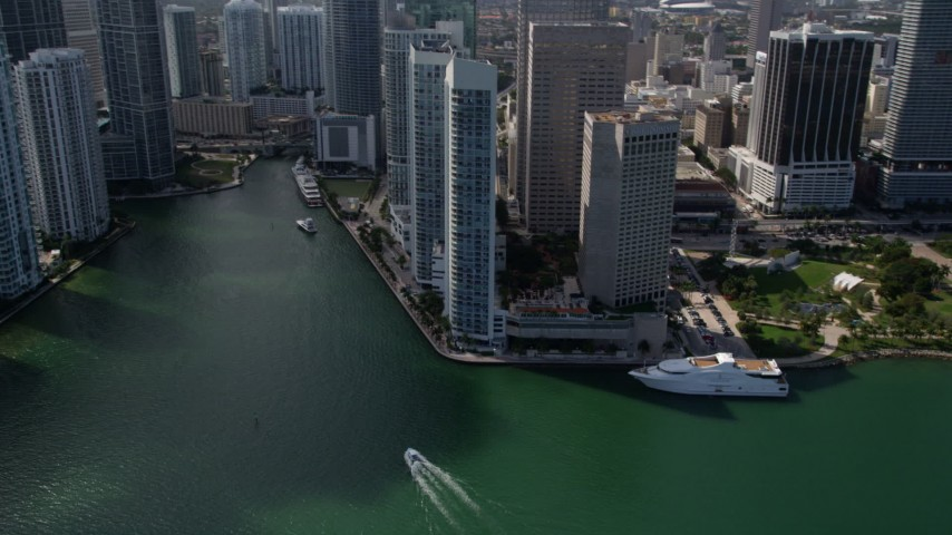 5K stock footage aerial video tilt from fishing boats in the bay to reveal skyscrapers and river in Downtown Miami, Florida Aerial Stock Footage | AX0020_026