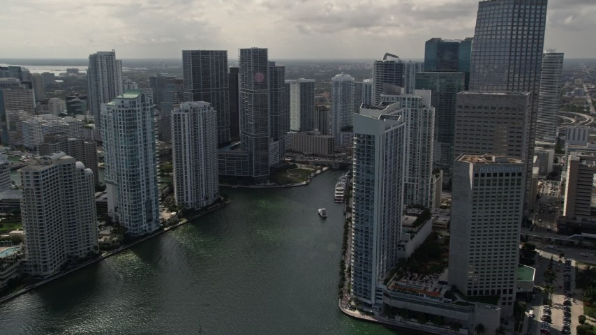 5K stock footage aerial video tilt from fishing boats in the bay to reveal skyscrapers and river in Downtown Miami, Florida Aerial Stock Footage | AX0020_026E
