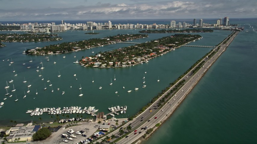 5K stock footage aerial video of MacArthur Causeway by sailboats moored in the bay, and Palm and Hibiscus Islands in Miami, Florida Aerial Stock Footage | AX0020_034