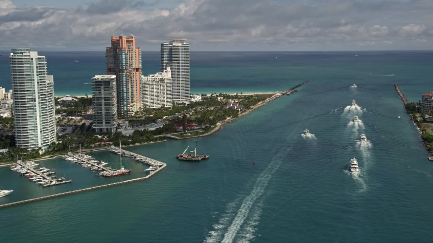 5K stock footage aerial video fly over ferries on Government Cut and tilt to reveal South Beach skyscrapers in Florida Aerial Stock Footage | AX0020_040