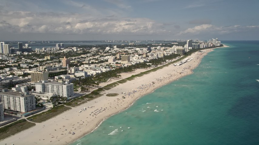5K stock footage aerial video tilt from sunbathers on the beach to a wider view of South Beach, Florida Aerial Stock Footage | AX0020_044