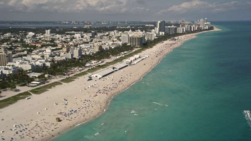 5K stock footage aerial video tilt from beachgoers and sunbathers to beachfront buildings in South Beach, Florida Aerial Stock Footage | AX0020_045