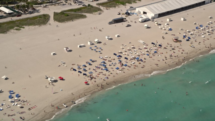 5K aerial video of sunbathers enjoying the beach and ocean in South Beach, Florida Aerial Stock Footage | AX0020_046