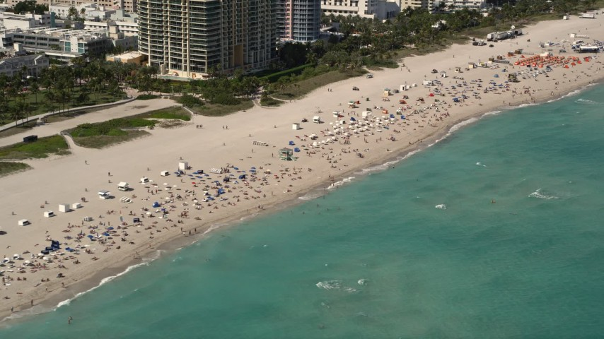 5K stock footage aerial video of large group of sunbathers and beachgoers by the ocean in South Beach, Florida Aerial Stock Footage | AX0020_047
