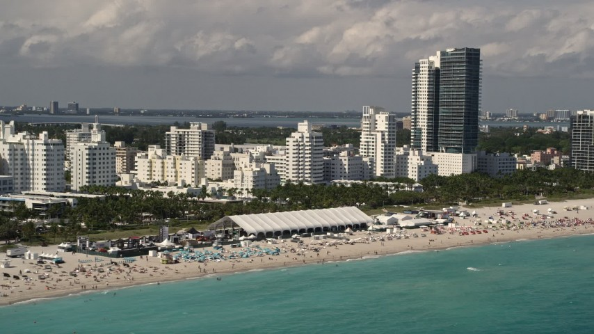 5K stock footage aerial video of crowd of sunbathers near beachfront hotels in Miami Beach, Florida Aerial Stock Footage | AX0020_048
