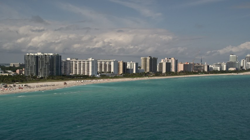 5K stock footage aerial video of a row of beachfront condominium complexes in Miami Beach, Florida Aerial Stock Footage | AX0020_049
