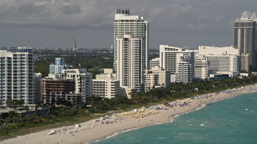 5K stock footage aerial video approach beachfront Fontainebleau Miami Beach Hotel with crowded beach in Florida Aerial Stock Footage | AX0020_051E