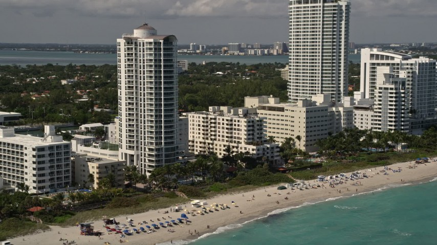 5K stock footage aerial video of beachfront hotels and sunbathers by the ocean in Miami Beach, Florida Aerial Stock Footage | AX0020_053