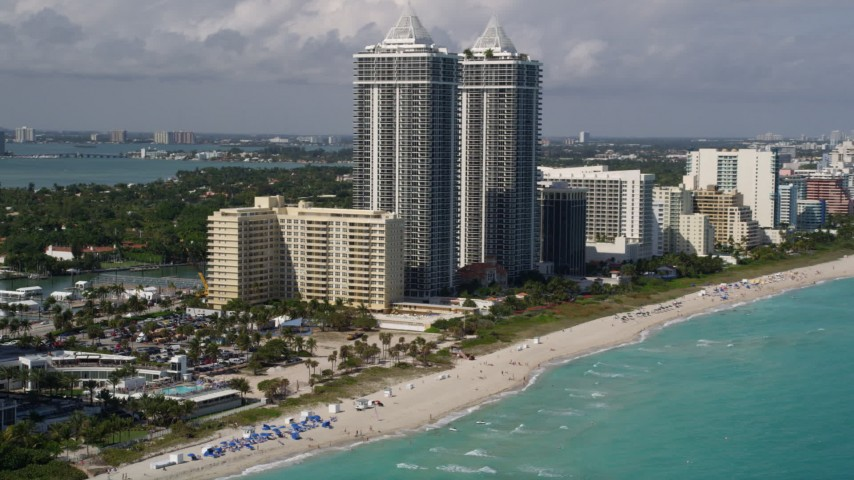 5K stock footage aerial video tilt from beachfront skyscrapers to sunbathers on the beach in Miami Beach, Florida Aerial Stock Footage | AX0020_055